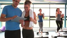Vrouwen die aerobics doen terwijl trainer die met vrouw spreken stock videobeelden
