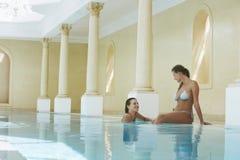 Vrouwen die bij Rand van Zwembad spreken royalty-vrije stock fotografie