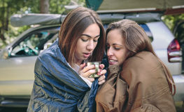 Vrouwen die binnen van slaapzakken koffiekop houden stock afbeelding