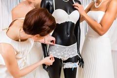 Vrouwen die bruids lingerie in huwelijkswinkel selecteren Royalty-vrije Stock Afbeelding