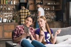 Vrouwen die CD-doos bespreken terwijl thuis het zitten op bank Stock Afbeeldingen