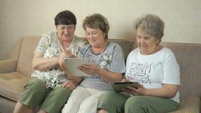 Vrouwen die de zilveren digitale tabletten houden stock videobeelden