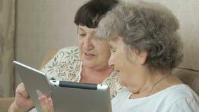 Vrouwen die de zilveren digitale tabletten houden stock video