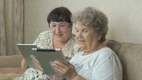 Vrouwen die de zilveren digitale tabletten houden stock footage