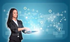 Vrouwen die digitale tablet en wereldkaart gebruiken met Royalty-vrije Stock Foto's