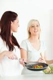 Vrouwen die diner koken Stock Afbeeldingen