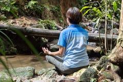 Vrouwen die door de rivier mediteren Stock Afbeeldingen