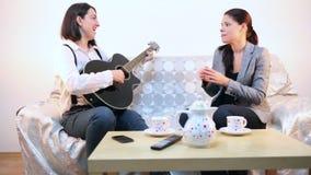 Vrouwen die een lied op gitaar en stem spelen stock videobeelden