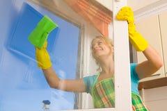 Vrouwen die een venster schoonmaken royalty-vrije stock afbeeldingen