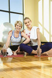Vrouwen die en bij Gymnastiek zitten glimlachen Royalty-vrije Stock Foto's