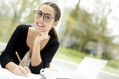 Vrouwen die en in blocnote glimlachen schrijven Stock Afbeeldingen