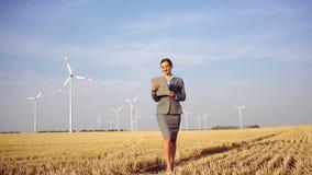 Vrouwen die geld zetten in een ethische Investering van windturbines stock footage