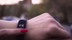 Vrouwen die geschiktheidsarmband gebruiken De atleet die van de sleepagent haar slim horloge app met behulp van om geschiktheidsv stock video
