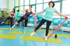Vrouwen die gymnastiekoefeningen doen die de banden van de latexgeschiktheid gebruiken Royalty-vrije Stock Afbeeldingen