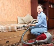 Vrouwen die haar woonkamer schoonmaken. Stock Afbeeldingen