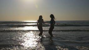 Vrouwen die in het water op de kust van een strand dansen - langzame motie stock video