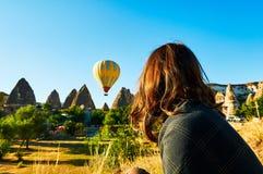 Vrouwen die Hete Luchtballon over blauwe turkooise hemel in Cappadocia Turkije zonsopgang bekijken royalty-vrije stock foto's