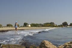 Vrouwen die in hoed blootvoetse op zee kust lopen Stock Foto's