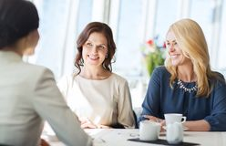Vrouwen die koffie drinken en bij restaurant spreken Stock Foto