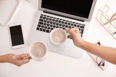 Vrouwen die koffiekoppen houden bij moderne werkplaats in bureau royalty-vrije stock foto's