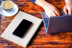 Vrouwen die laptop met koffie en slimme telefoon werken Stock Afbeelding