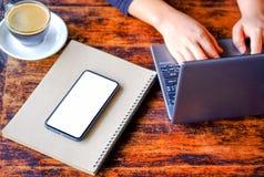 Vrouwen die laptop met koffie en slimme telefoon werken Stock Fotografie