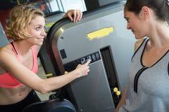 Vrouwen die machines in gymnastiek met behulp van stock fotografie