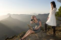 Vrouwen die met draagbare laptop in de berg werken Royalty-vrije Stock Foto's