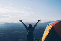 Vrouwen die met rugzak van zonsondergang op berg genieten Toeristenreiziger royalty-vrije stock afbeelding