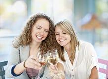 Vrouwen die met witte wijn roosteren Stock Fotografie