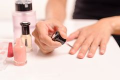 Vrouwen die nagellak op witte lijst met flessen van nagellak en vlekkenmiddel, manier en schoonheidsconcept toepassen royalty-vrije stock foto