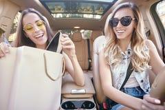 Vrouwen die nieuwe aankoop na het winkelen bekijken stock foto