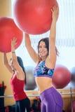 Vrouwen die oefeningen doen bij de gymnastiek op een Pilates-klasse Stock Afbeeldingen