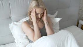 Vrouwen die op bed zitten die haar hoofd houden Zij heeft een pijnlijke hoofdpijn stock footage