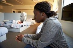 Vrouwen die op Bedden in Dakloze Schuilplaats zitten royalty-vrije stock afbeeldingen