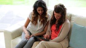 Vrouwen die op de bank zitten die een tabletcomputer houden stock video