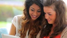 Vrouwen die op laag het lachen zitten stock videobeelden