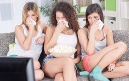 Vrouwen die op laag zitten die op droevige gedeprimeerde film letten Stock Foto's