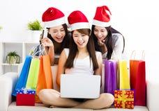 vrouwen die op laptop met Kerstmis het winkelen concept letten Stock Foto's