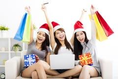 vrouwen die op laptop met Kerstmis letten die concep winkelen Stock Foto