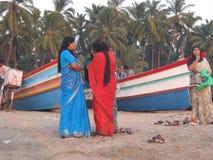 Vrouwen die op strand converseren Stock Afbeeldingen