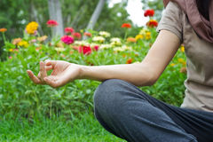 Vrouwen die in openlucht op de achtergrond van het bloempark mediteren royalty-vrije stock foto