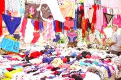 Vrouwen die openluchtmarktkraam kleden Stock Afbeeldingen