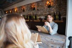 Vrouwen die orde in restaurant maken royalty-vrije stock afbeeldingen