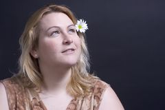Vrouwen die over bloem denken Stock Afbeeldingen