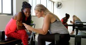Vrouwen die over mobiele telefoon 4k bespreken stock videobeelden