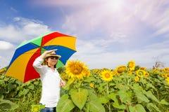 Vrouwen die paraplu met gebied het bloeien van zonnebloemen houden Royalty-vrije Stock Afbeeldingen