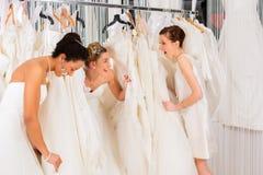 Vrouwen die pret hebben tijdens bruids kledingsmontage in winkel Royalty-vrije Stock Foto