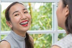 Vrouwen die rode lippenstift toepassen De schoonheidsvrouw neemt lippenstift, Meisjesvrienden die met samenstelling helpen Meisje royalty-vrije stock foto's