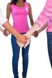 Vrouwen die roze en linten voor de holdingshanden van borstkanker dragen Stock Fotografie